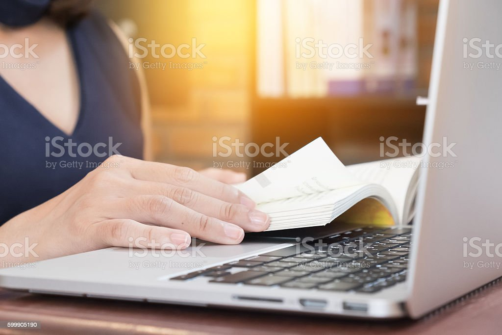 Close up of student hand reading a book at library stock photo