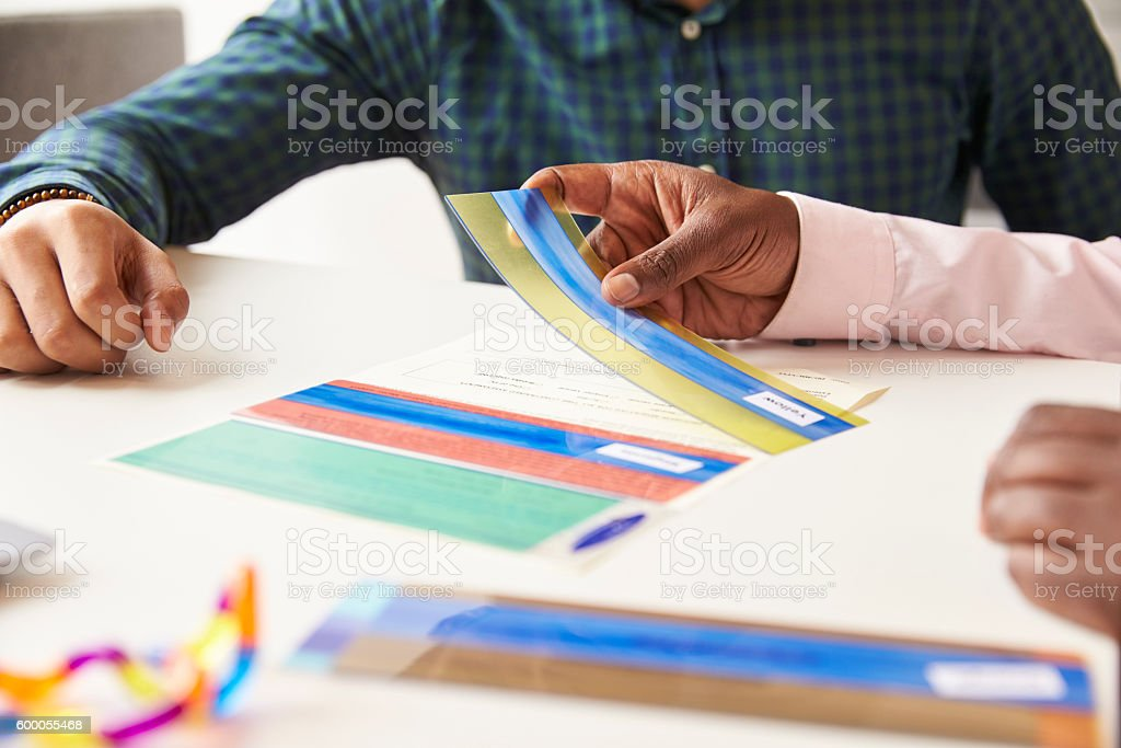 Close Up Of Student With Dyslexia Using Colored Overlays stock photo
