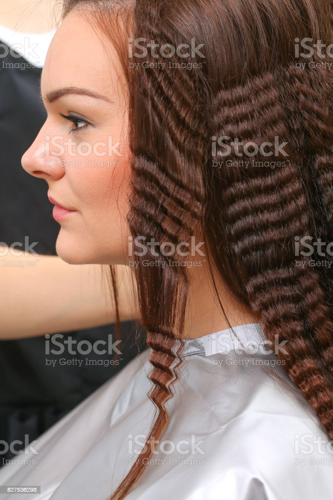 Close up of stylist hands with styling iron straightening woman hair at salon stock photo