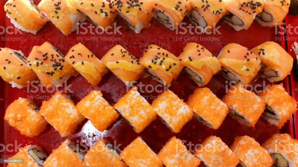 close up of sushi rolls on red tray on the table. Various delicious Types of Sushi Rolls. Top view flat lay stock photo