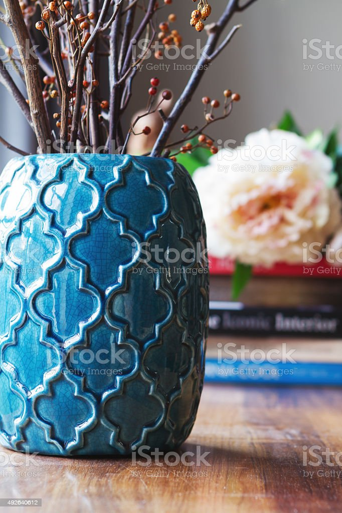 Close up of teal moroccan vase with sticks and decor stock photo