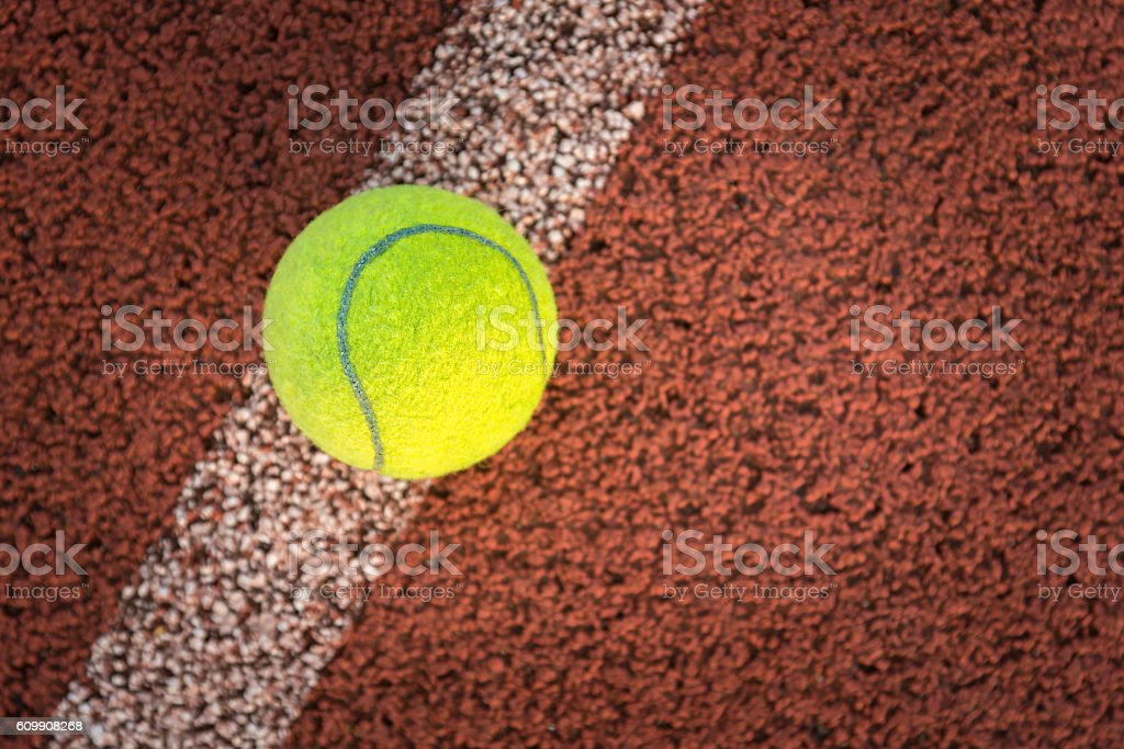 Close up of tennis ball on clay court./Tennis ball stock photo