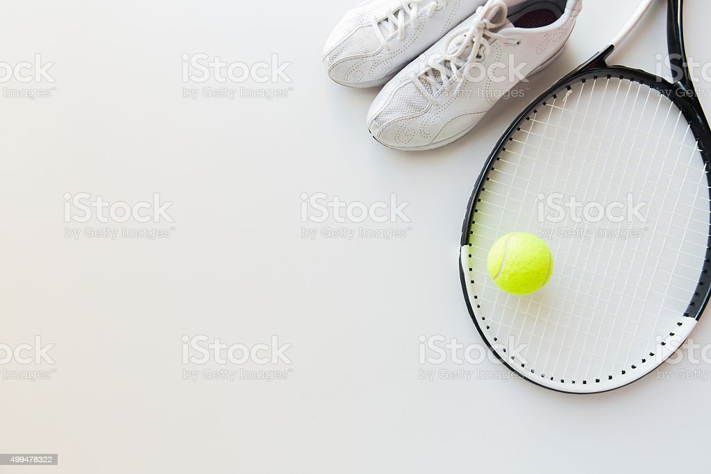 close up of tennis racket with ball and sneakers stock photo