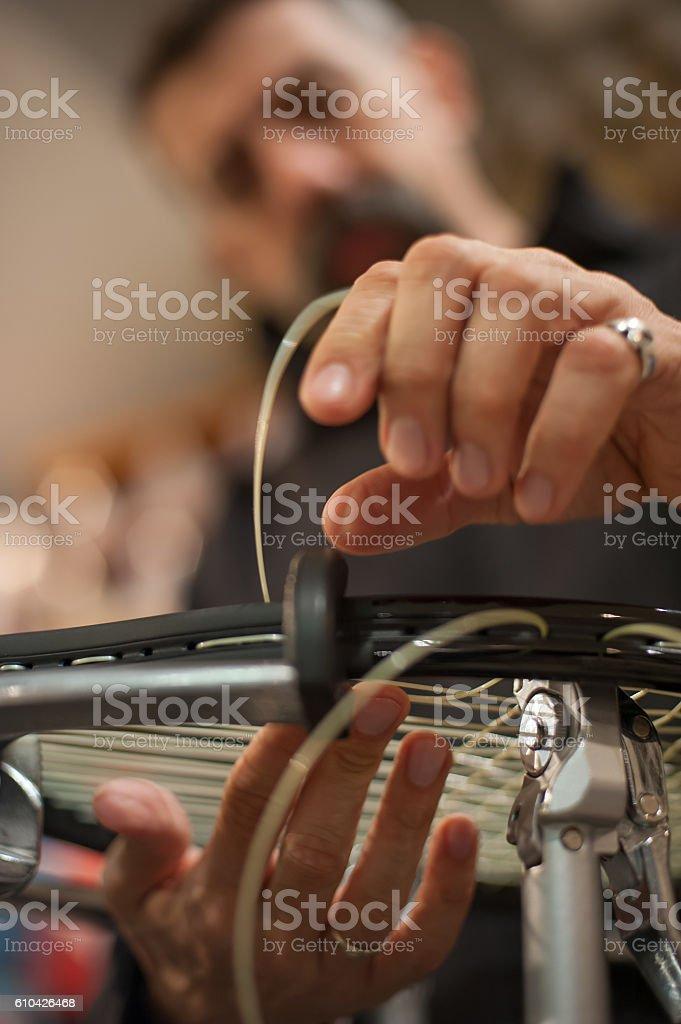 Close up of tennis stringer hands doing racket stringing stock photo