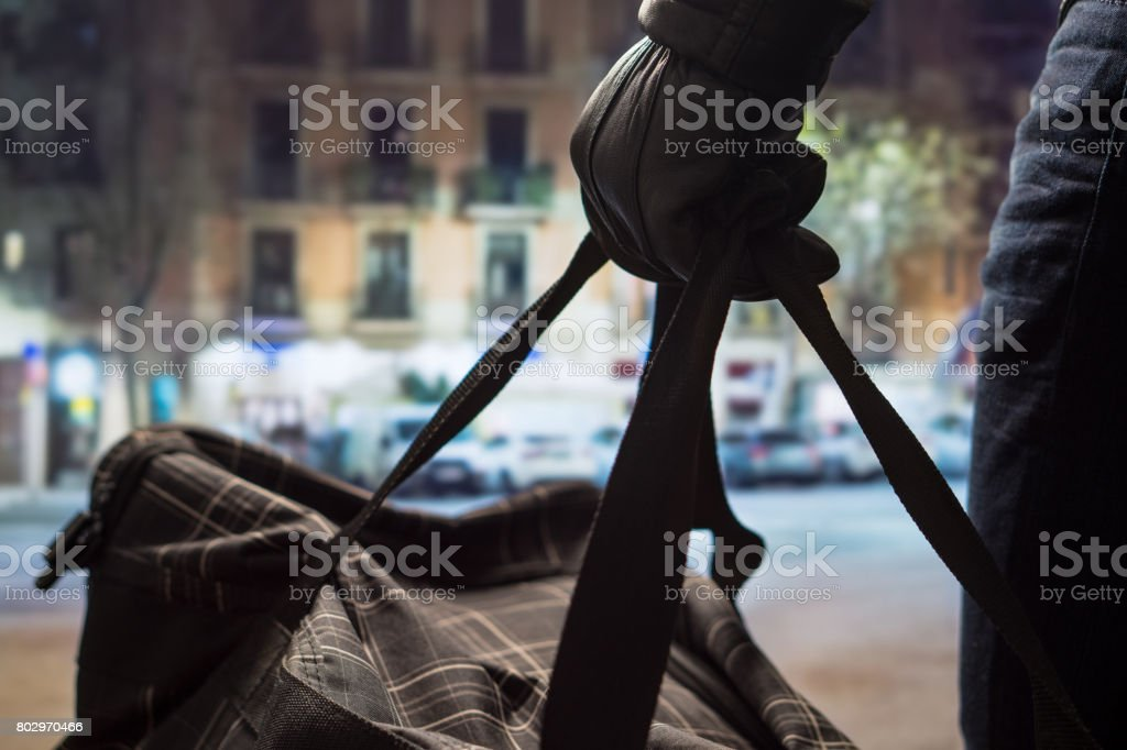 Close up of terrorist holding black bag in hand, possibly timebomb. Man planning a dangerous explosion in city center. Suicide bomber at night. Terrorism and security concept. stock photo