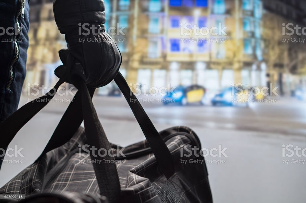 Close up of terrorist holding black bomb bag in hand. Suicide bomber planning dangerous explosion in city center at night. Traffic, cars and buildings in background. Terrorism and security concept. stock photo