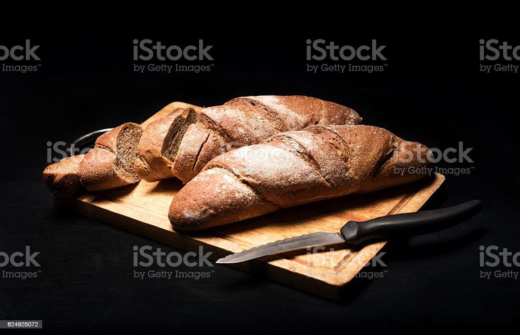 Close up of the baguette lying on a black background stock photo