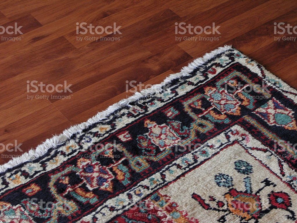 Close up of the corner on an oriental rug atop wood flooring royalty-free stock photo