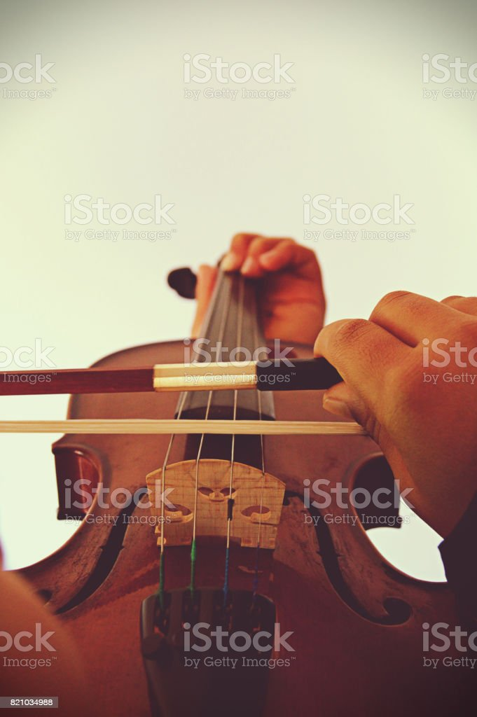 Close up of the hands playing the stringed and bowed musical instrument, the violin stock photo