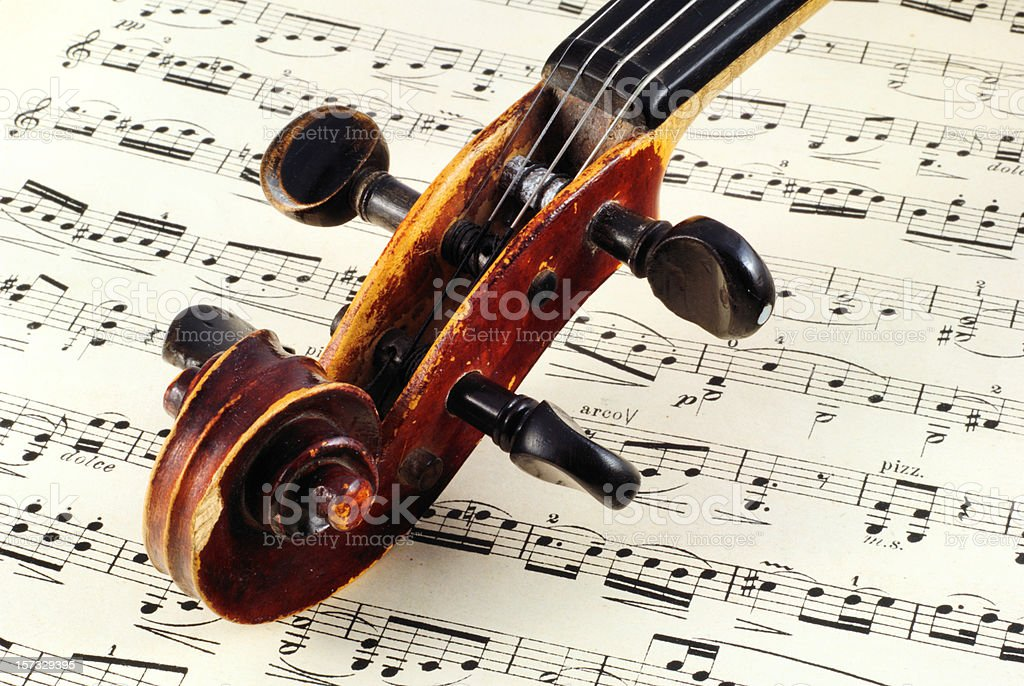 Close up of the top of a violin on a music sheet stock photo