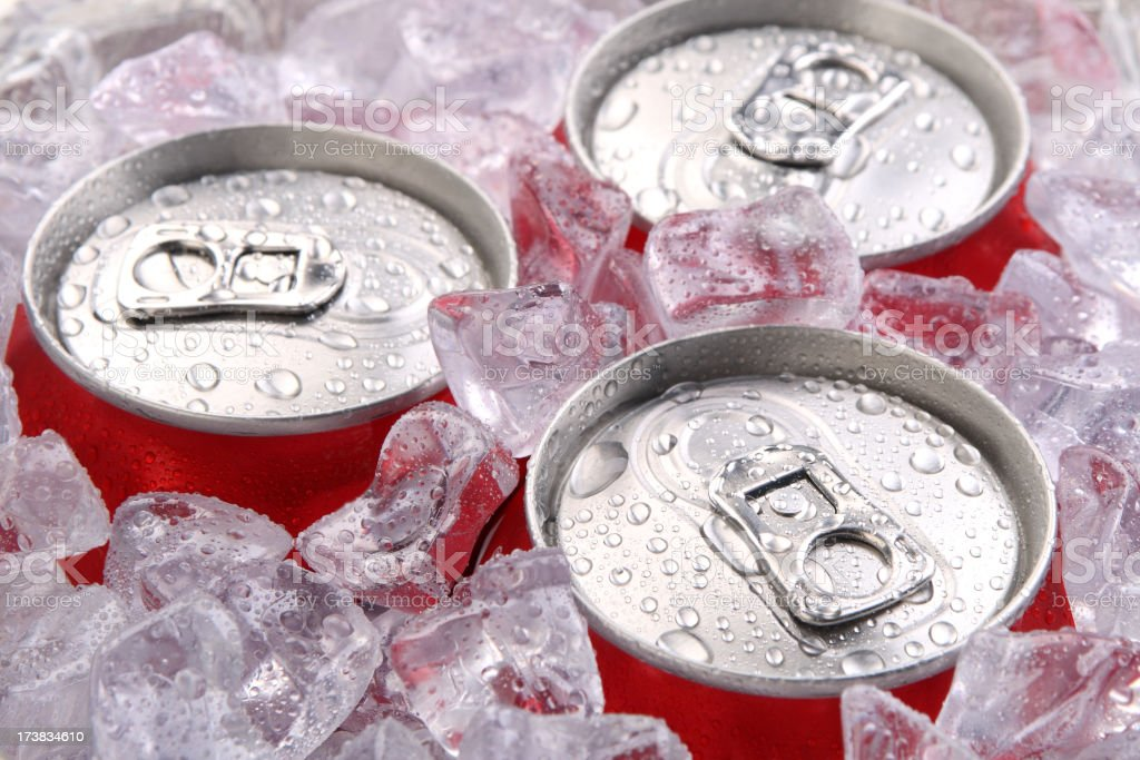 Close up of the tops of three soft drink cans in ice stock photo
