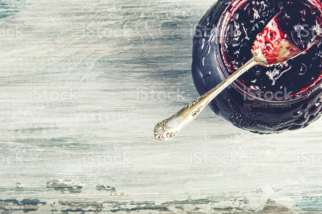 Close up of thick sweet strawberry jam with old spoon. stock photo