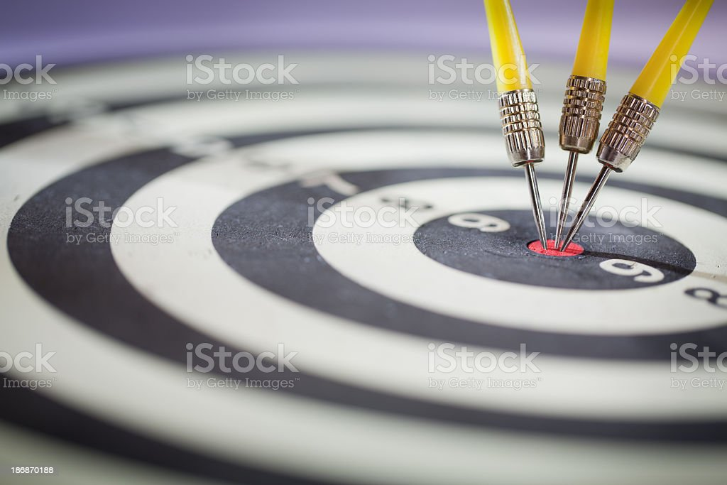Close up of three darts clustered in the bullseye royalty-free stock photo