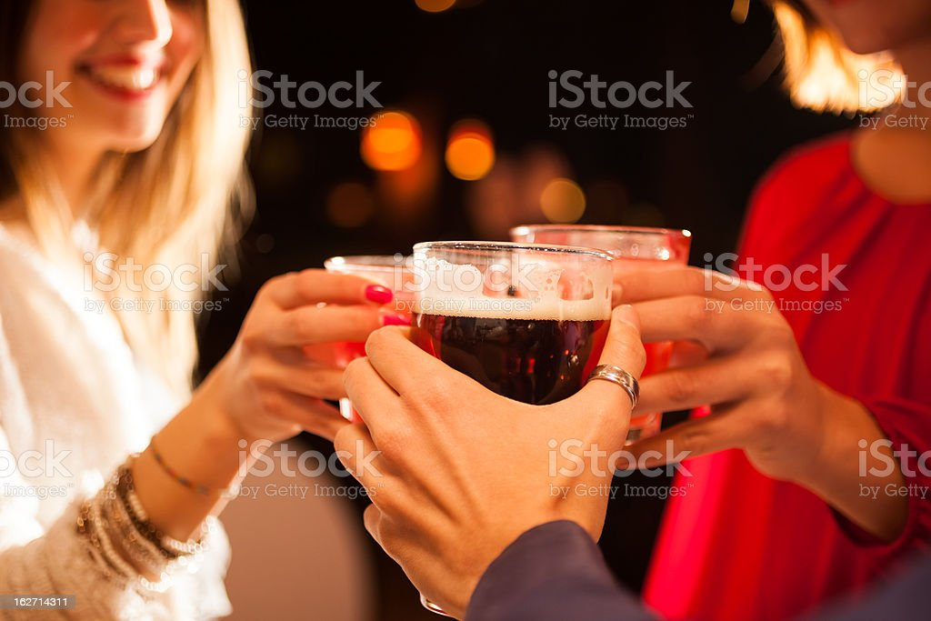Close up of three people toasting glasses stock photo