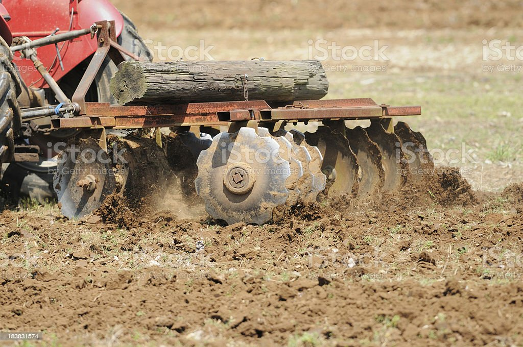 Close up of tilling field with tractor and disk harrow stock photo