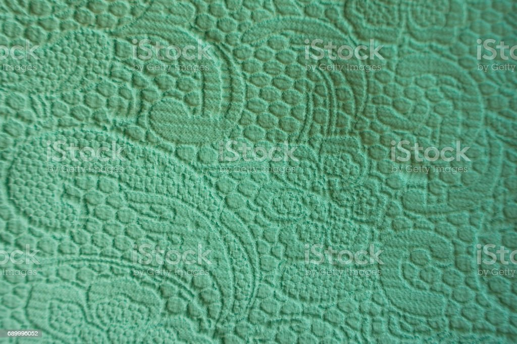 Close up of turquoise fabric with raised pattern with flowers and squiggles stock photo