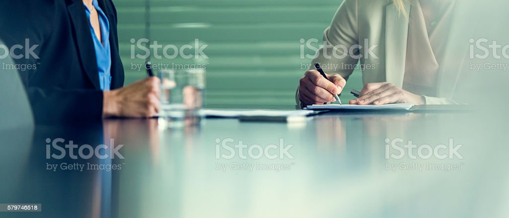 Close up of two businesswomen signing contracts at a conference stock photo