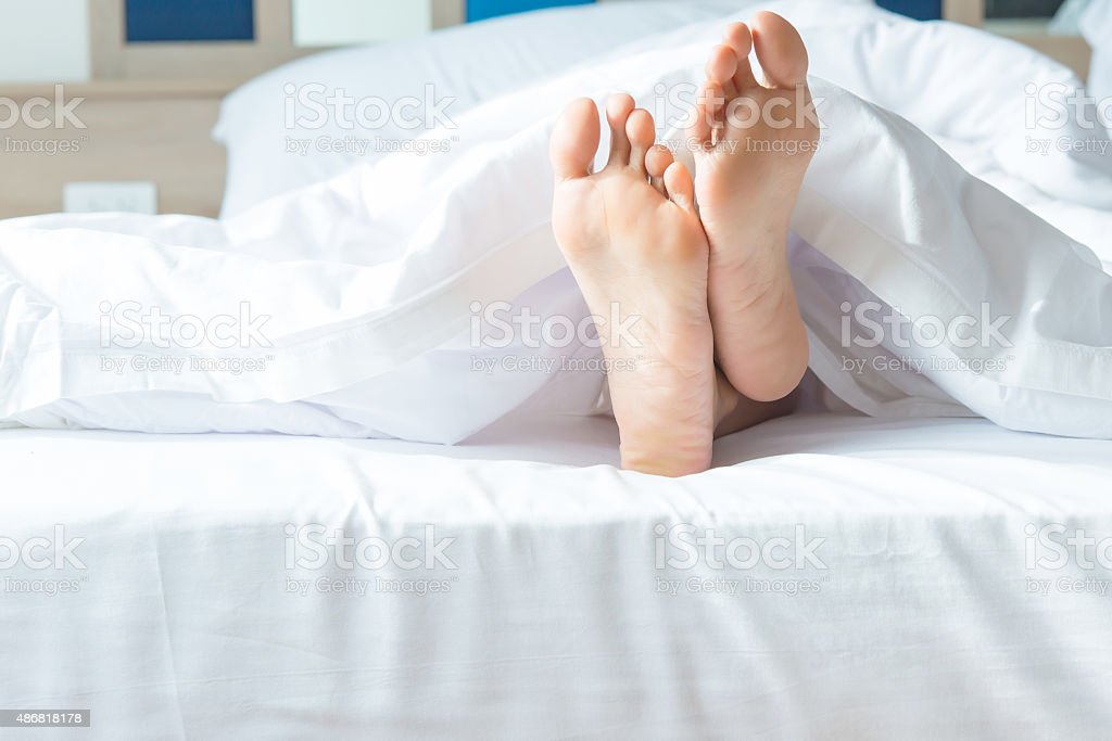 Close up of two feet in a bed.focus on feet stock photo