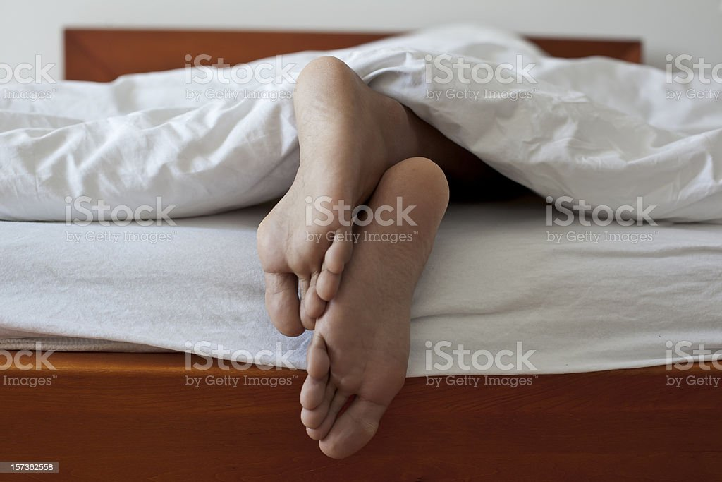 Close up of two feet in bed royalty-free stock photo
