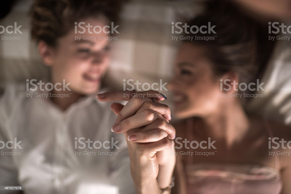 Close up of two female friends holding hands. stock photo