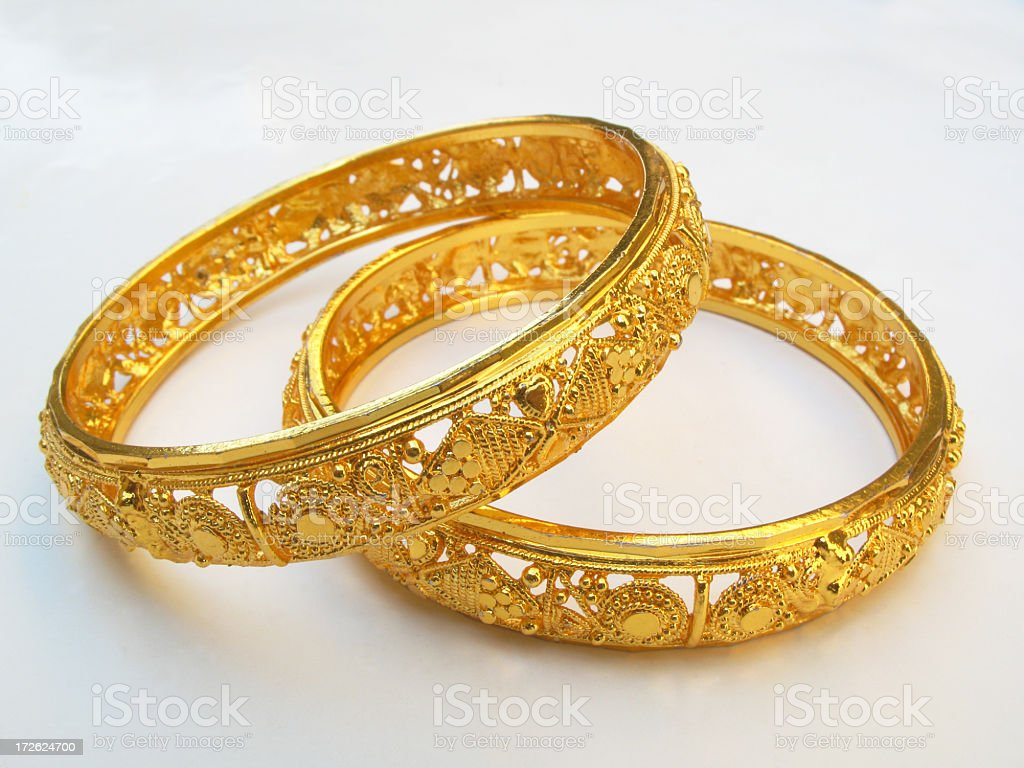 Close up of two gold bangles with intricate pattern stock photo
