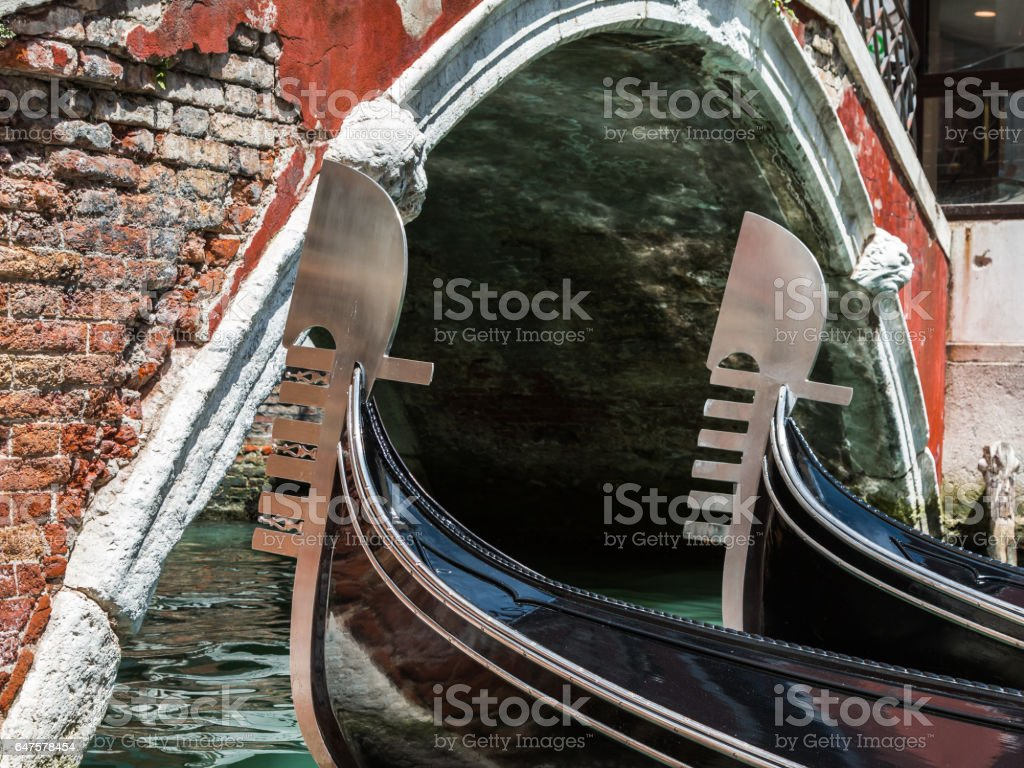 Close up of Two Gondola's Iron Prow and Antique Red Bridge in Venice, Italy stock photo