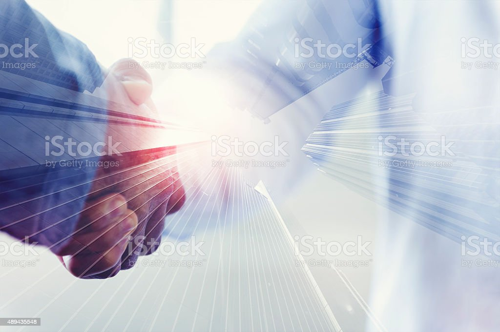 Close up of two people shaking hands with city stock photo