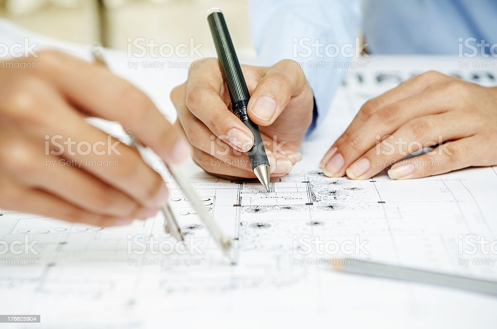 Close up of two people's hand sketching on drawing plan royalty-free stock photo