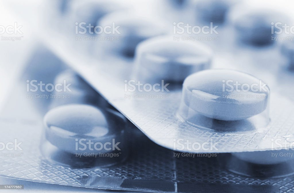 Close up of two unopened pill packs with pale blue pills stock photo
