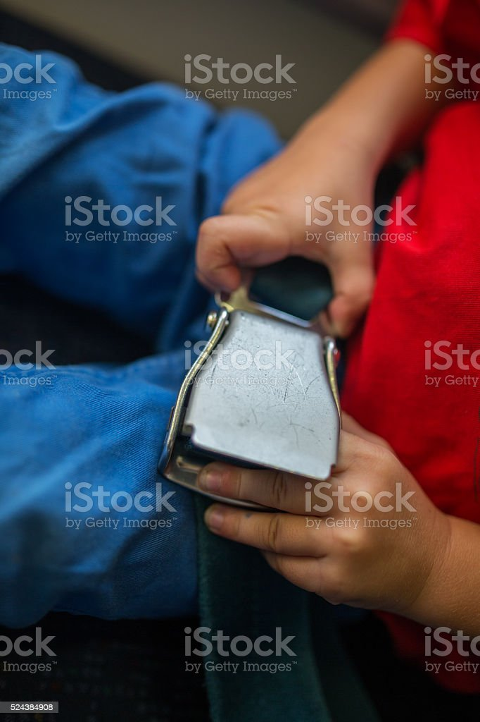 Close up of unrecognizable child fastening seatbelt in airplane. stock photo