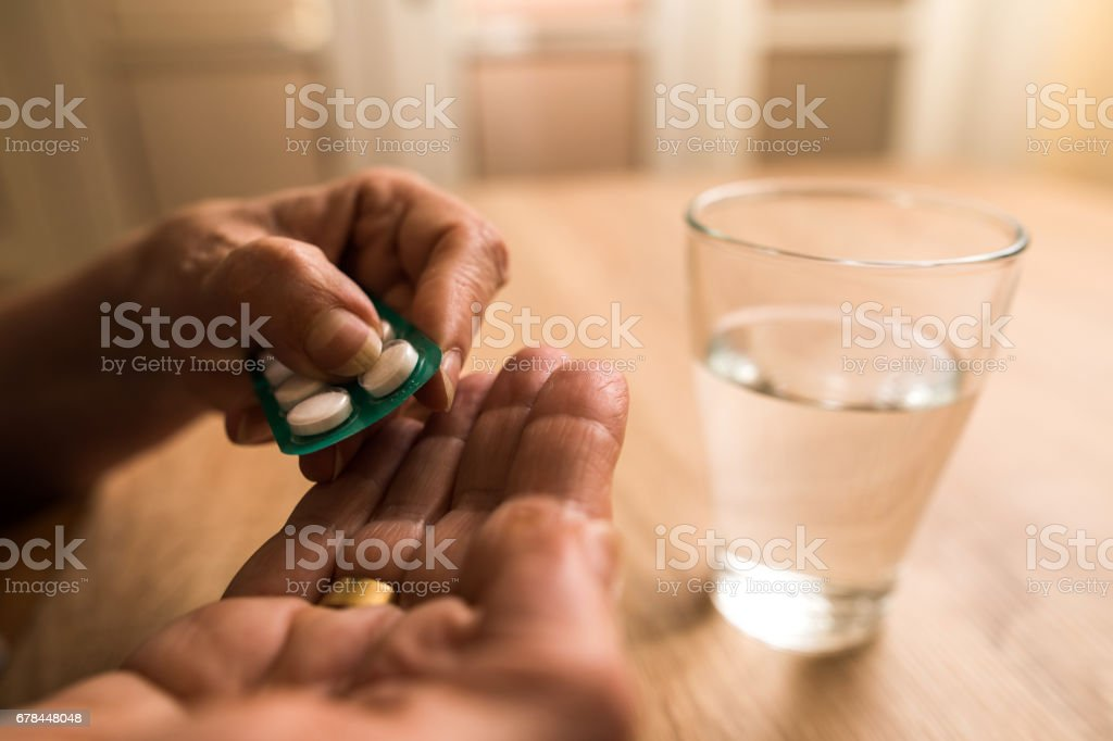 Close up of unrecognizable elderly person taking pills. stock photo