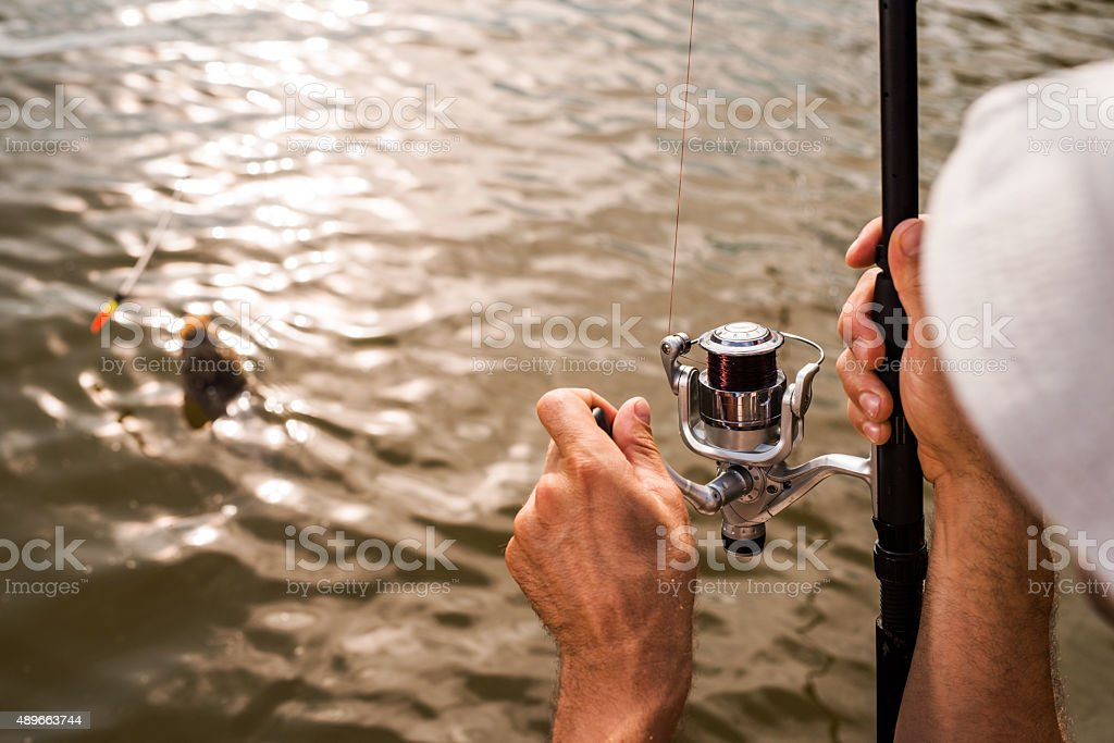 Close up of unrecognizable fisherman catching a fish. stock photo