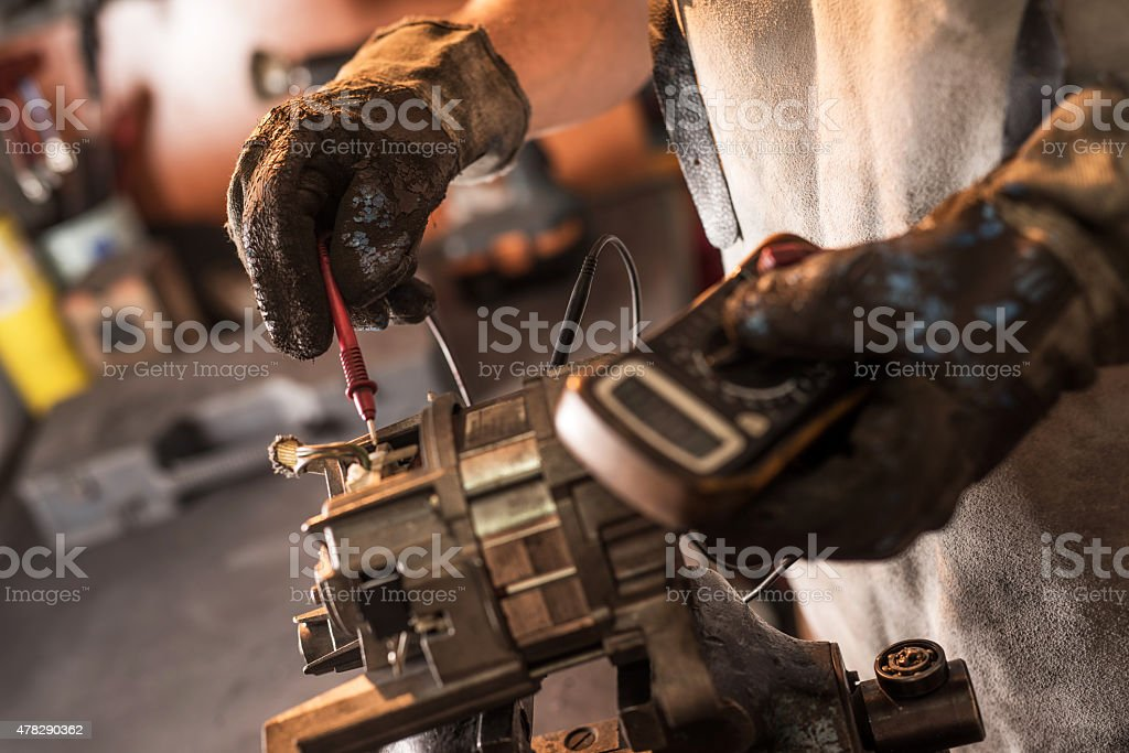 Close up of unrecognizable machinist examining electric motor with voltmeter. stock photo