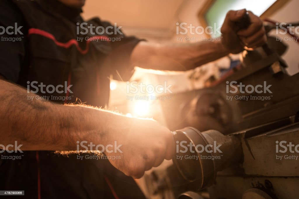 Close up of unrecognizable machinist working on drill bit. stock photo
