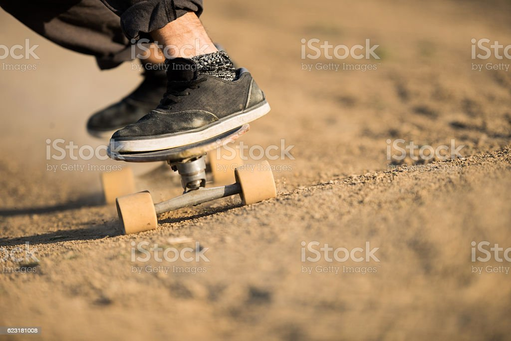 Close up of unrecognizable man skateboarding on a dirt road. stock photo