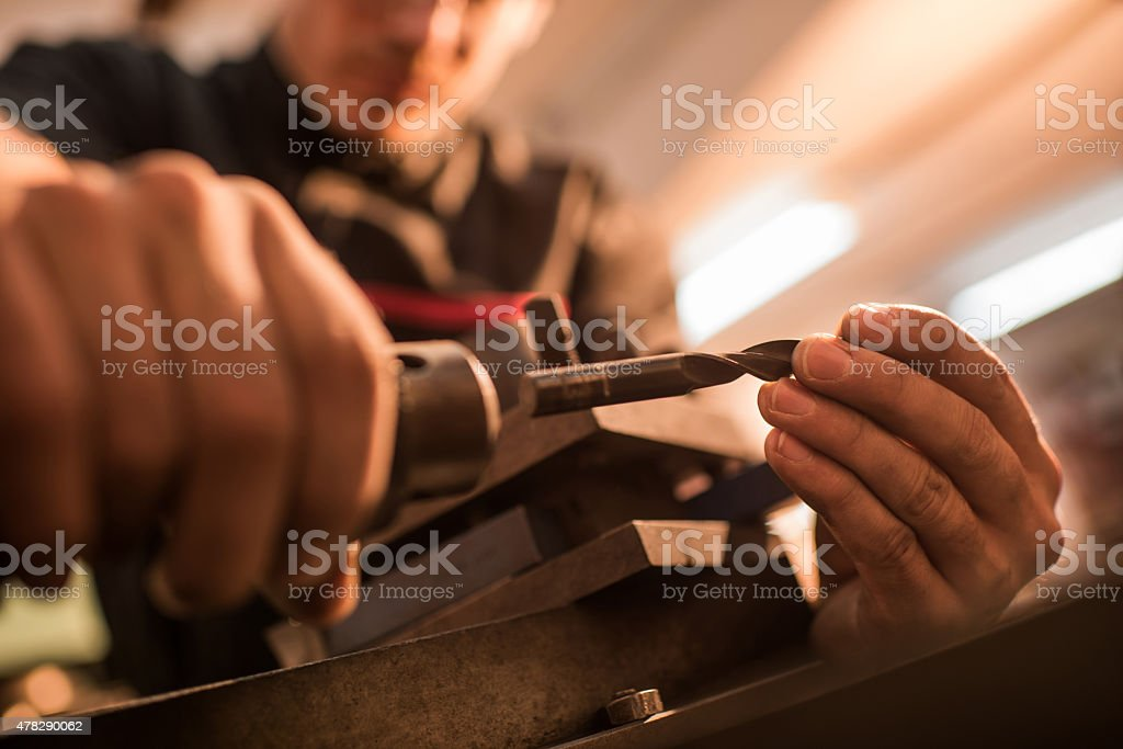 Close up of unrecognizable mechanic preparing lathe machine for work. stock photo