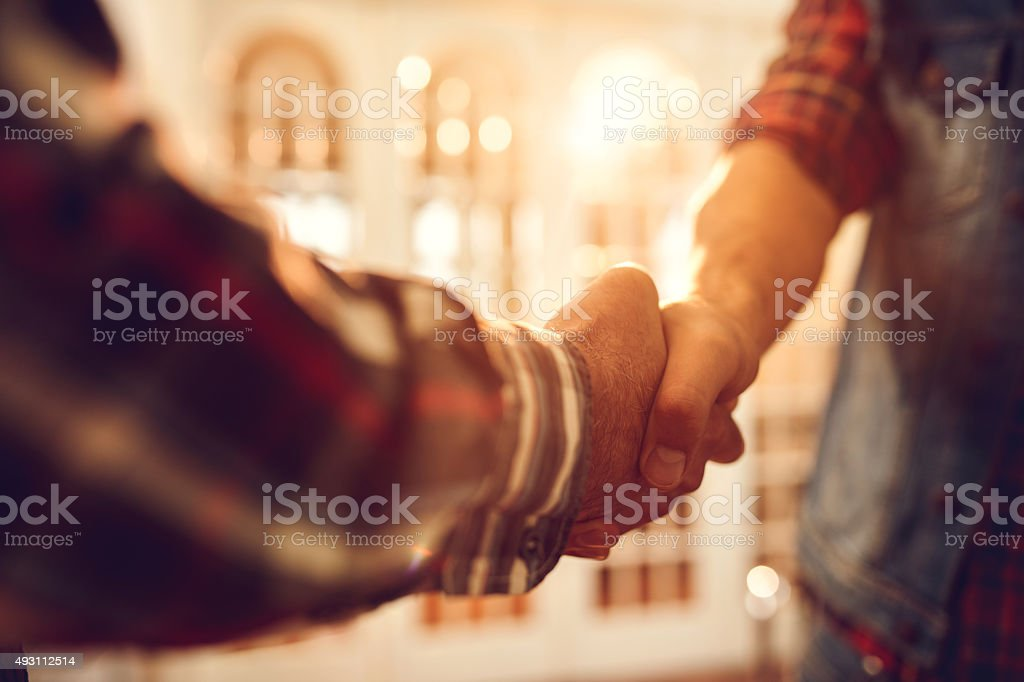 Close up of unrecognizable men come to an agreement. stock photo