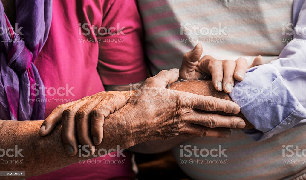 Close up of unrecognizable older couple holding hands. stock photo