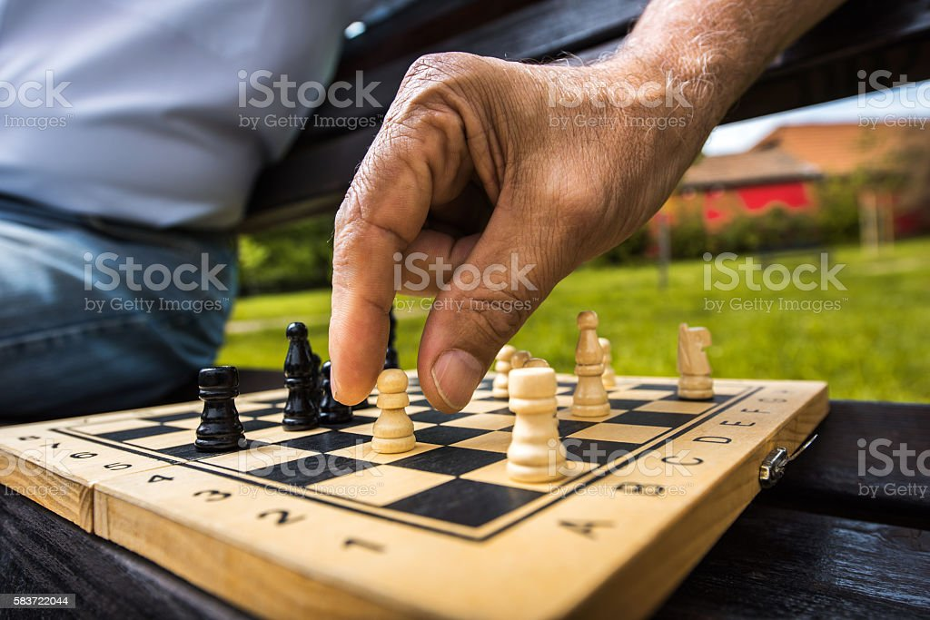 Close up of unrecognizable person playing chess in nature. stock photo
