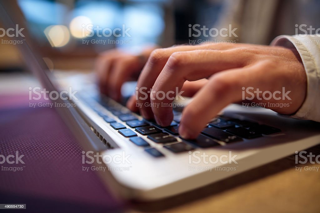 Close up of unrecognizable person typing on laptop. stock photo