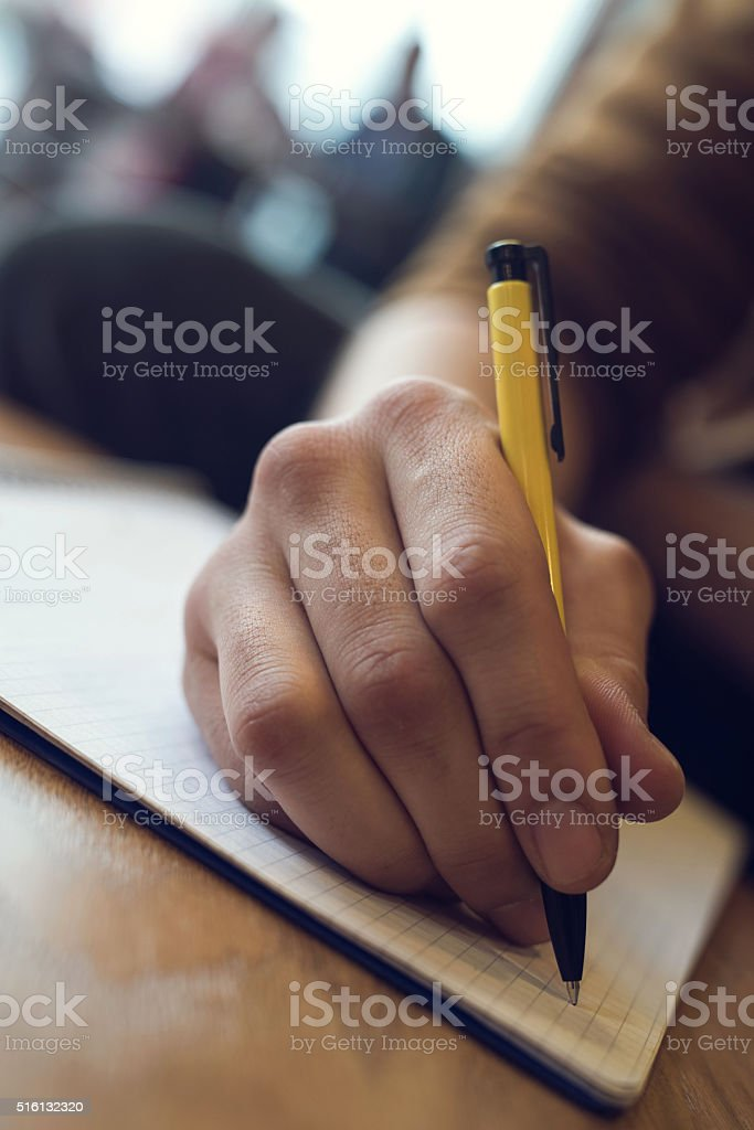 Close up of unrecognizable person writing in a notebook. stock photo