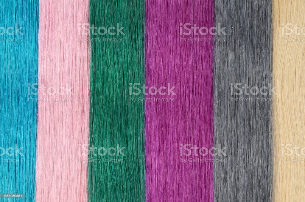 close up of various colors of straight human hair extensions stock photo