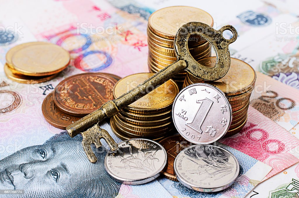 Close up of Vintage key with coins stack and china banknote stock photo