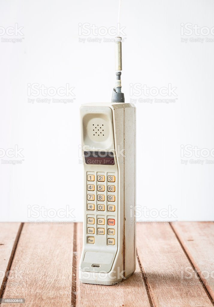 Close up of vintage mobile phone on wooden countertop stock photo