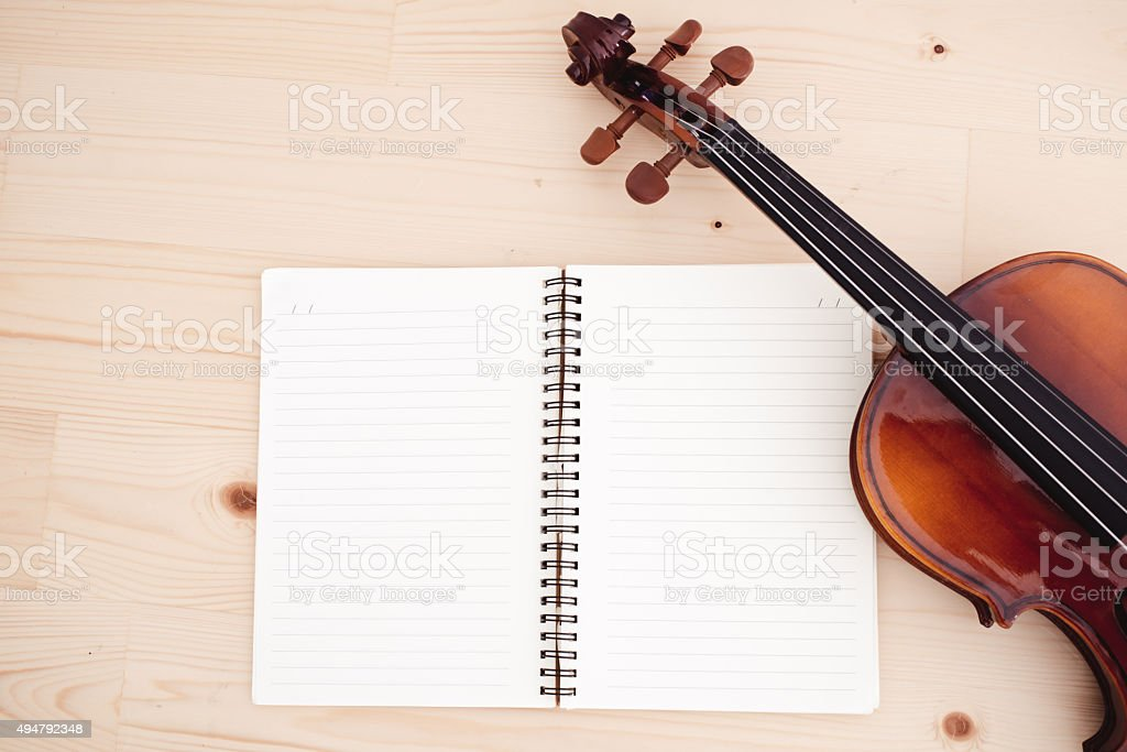 Close up of violin and book on pine table stock photo