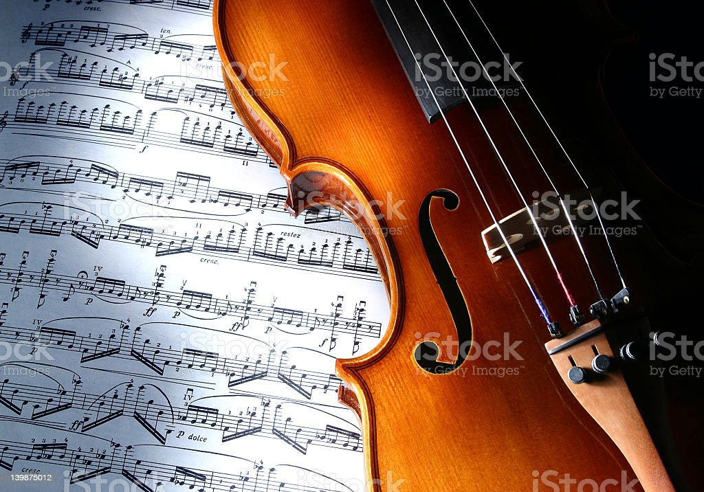 Close up of violin on top of music book showing music notes royalty-free stock photo