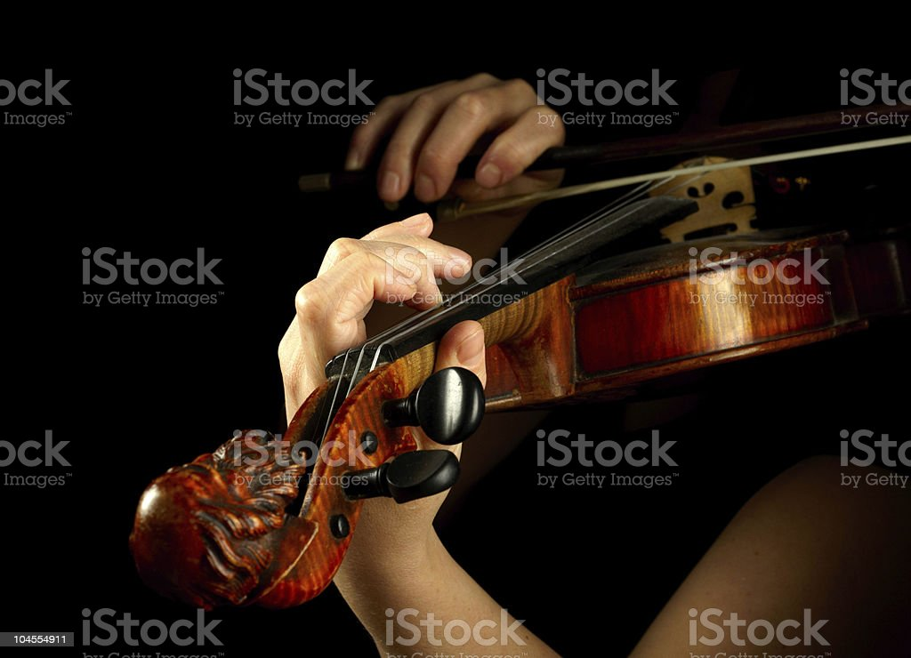 Close up of violinist's hands and bow with dark background royalty-free stock photo