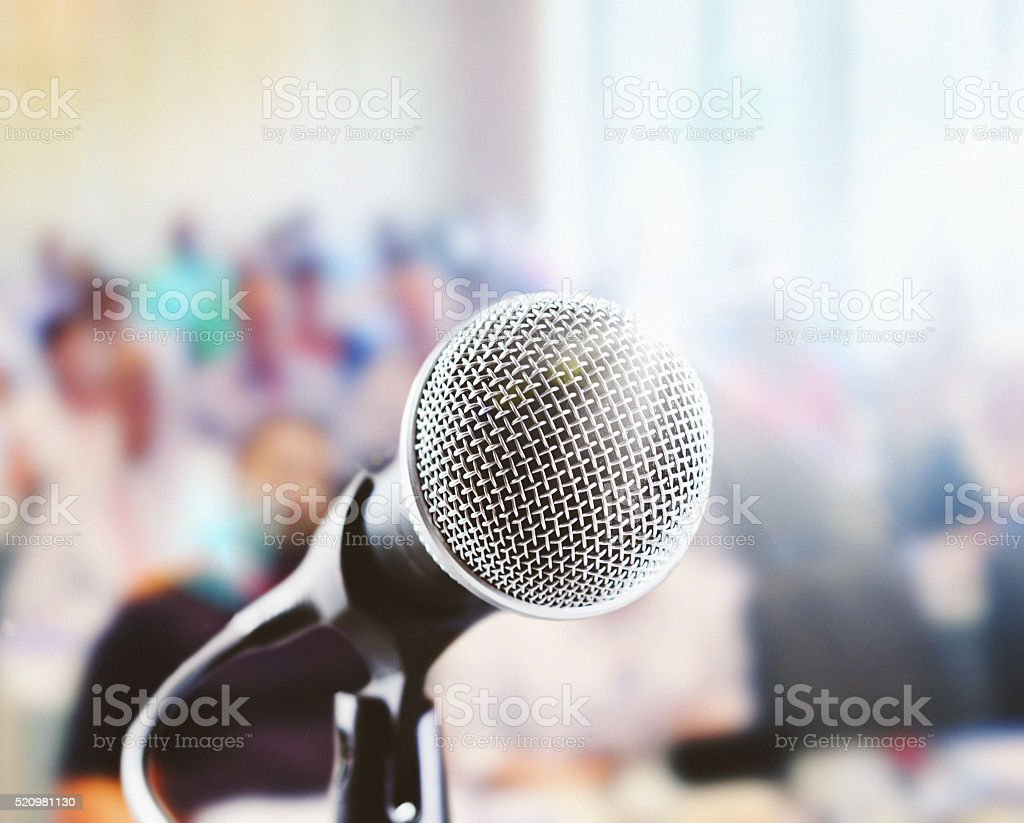 Close up of retro-style vocal mic with defocussed audience stock photo