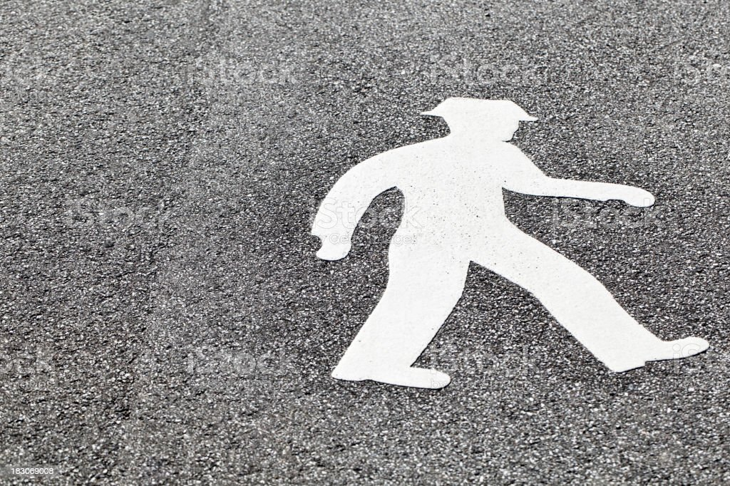 Close up of white pedestrian symbol. Road marking. royalty-free stock photo