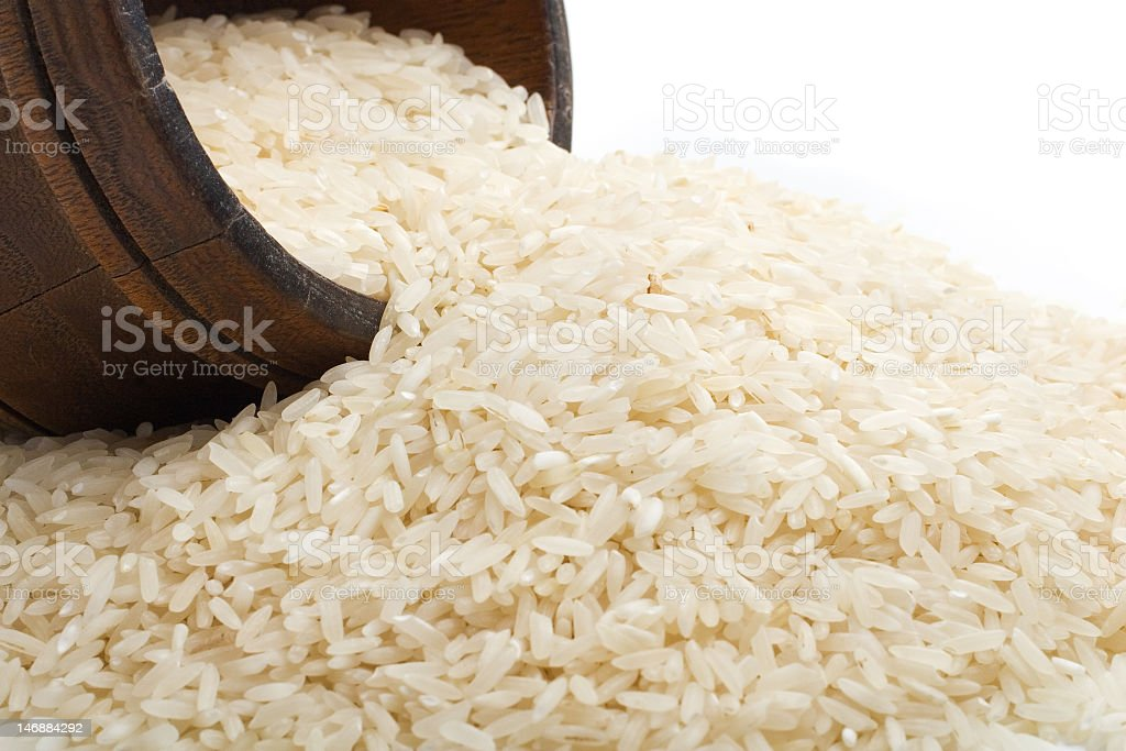 Close up of white rice grains spilling out from a barrel stock photo